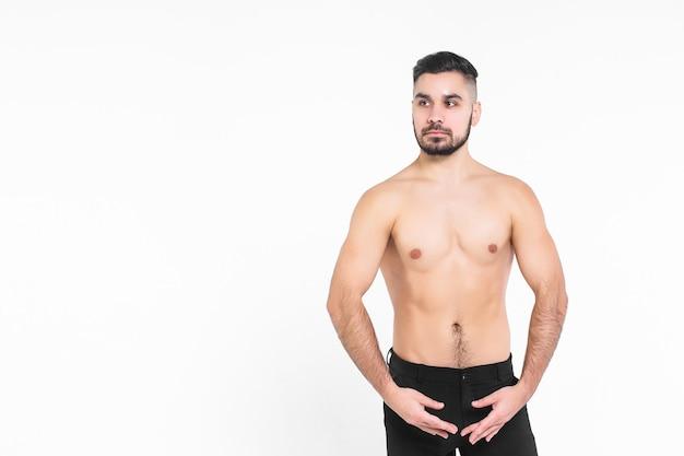 Młody mężczyzna odizolowany na białej ścianie, ubrany w czarne spodnie z nagim torsem