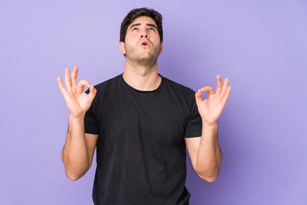 Młody mężczyzna odizolowywający na purpurach relaksuje po ciężkiego pracującego dnia, wykonuje joga.
