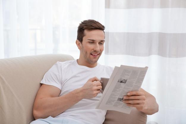 Młody mężczyzna odpoczywający na kanapie z gazetą i pijący herbatę w jasnym pokoju