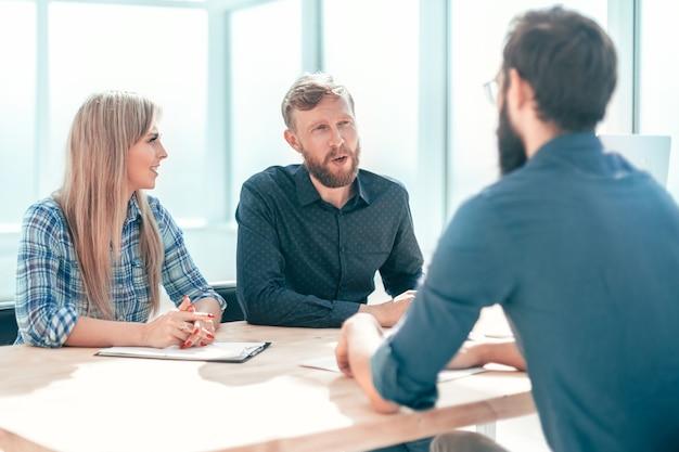 Młody mężczyzna odpowiada na pytania menedżerów podczas rozmowy kwalifikacyjnej. pojęcie zatrudnienia