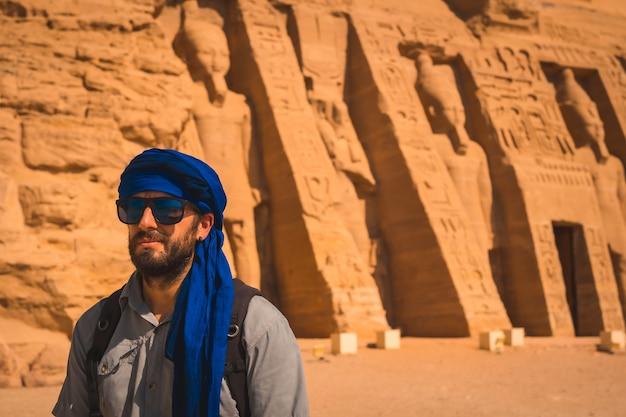 Młody mężczyzna odwiedzający zrekonstruowaną świątynię nefertari w pobliżu abu simbel w południowym egipcie w nubii nad jeziorem naser. świątynia faraona ramzesa ii, podróżniczy styl życia