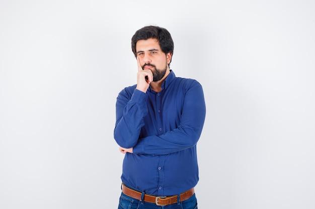 Młody mężczyzna odwracając się z ręką na twarzy w królewskiej niebieskiej koszuli i patrząc zamyślony, widok z przodu.