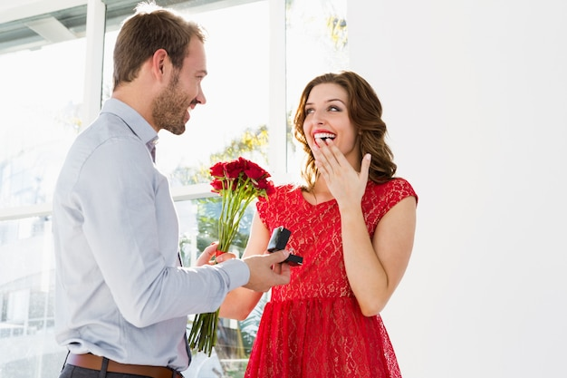 Młody mężczyzna oferujący kwiaty i pierścionek zaręczynowy do pięknej kobiety