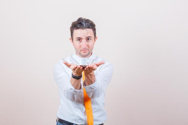 Młody mężczyzna oferuje filiżankę tureckiej kawy w białej koszuli, krawacie i wygląda delikatnie