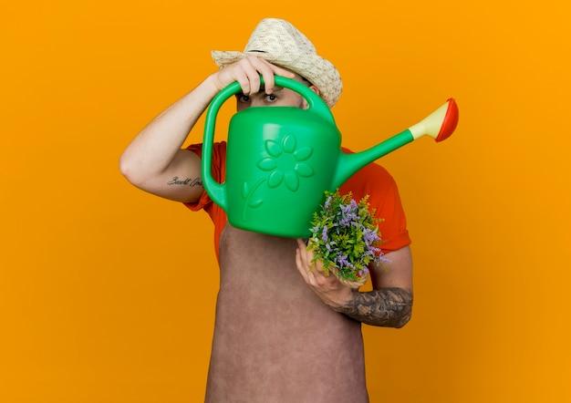 Młody mężczyzna ogrodnik w kapeluszu ogrodniczym trzyma kwiaty w doniczce i patrzy przez konewkę