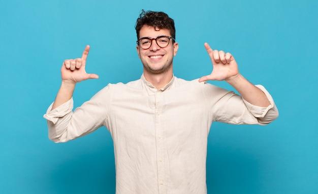 Młody mężczyzna oprawiający lub zarysowujący swój uśmiech obiema rękami .