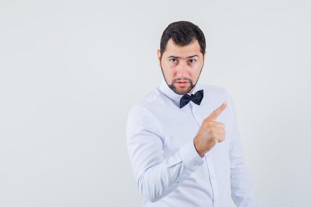 Młody mężczyzna ostrzeżenie z palcem w białej koszuli i patrząc poważny, przedni widok.