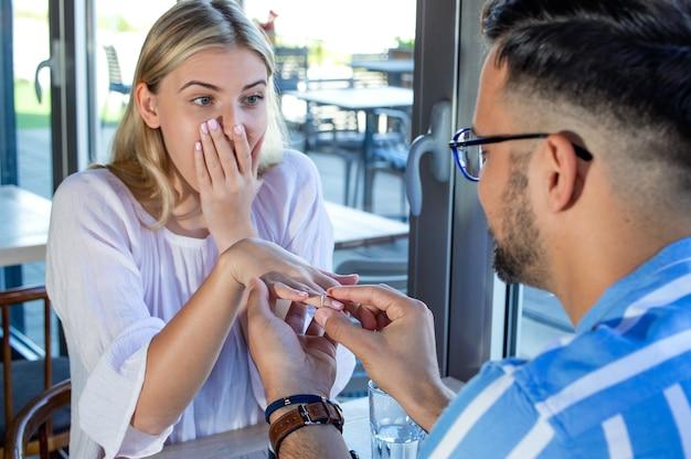 Młody mężczyzna oświadcza się swojej zachwyconej dziewczynie w restauracji z pierścionkiem zaręczynowym z brylantem