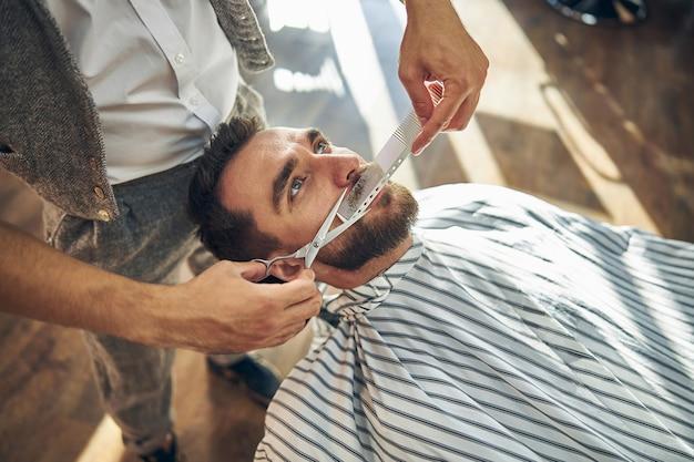Młody mężczyzna otrzymujący wąsy od profesjonalnego fryzjera