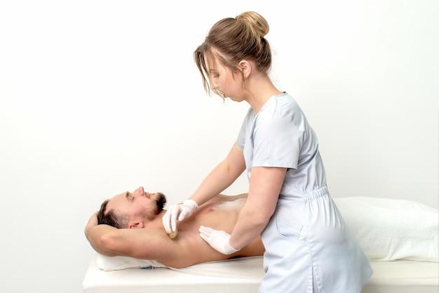 Młody mężczyzna otrzymujący wosk pod pachami lub depilację pod pachą przez młodą kosmetyczkę w salonie piękności