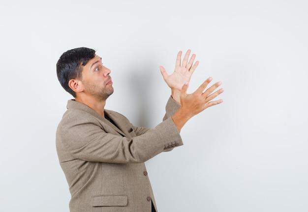 Młody mężczyzna otwiera ramiona na bok w szarawo brązowej kurtce, czarnej koszuli i wygląda dziwnie. .