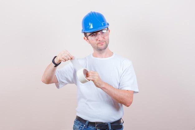 Młody mężczyzna otwiera rolkę taśmy klejącej w koszulce, dżinsach, kasku i wygląda ostrożnie