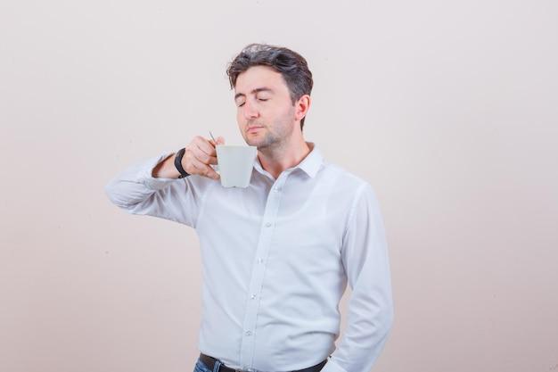 Młody mężczyzna pachnący aromatyczną herbatą w białej koszuli, dżinsach i wyglądający na zachwyconego
