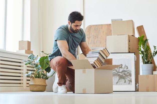 Młody mężczyzna pakujący książki w kartonowe pudła przenosi dom