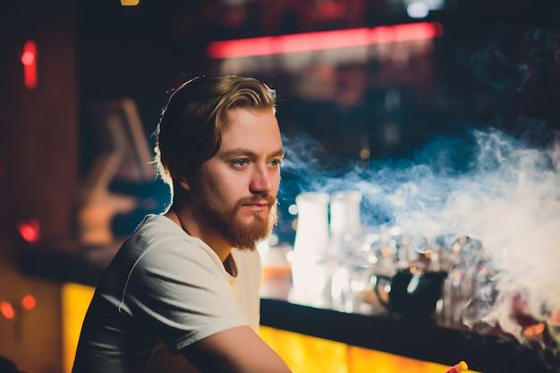 Młody mężczyzna palący sziszę w arabskiej restauracji - mężczyzna wydycha dym wdychając z fajki wodnej.