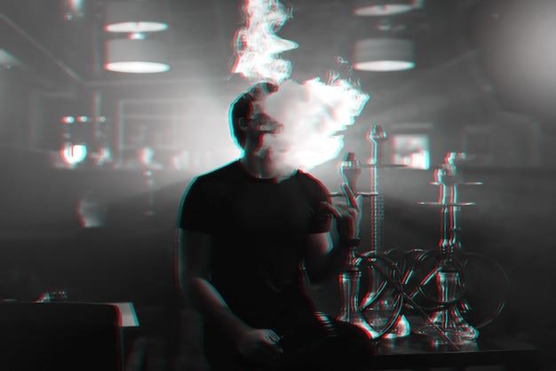 Młody mężczyzna pali fajkę wodną i wypuszcza chmurę dymu