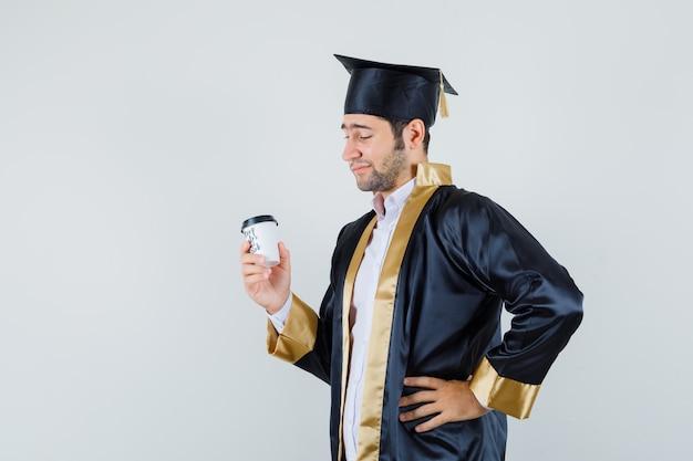 Młody mężczyzna patrząc na filiżankę kawy w mundurze absolwenta i patrząc zamyślony, widok z przodu.