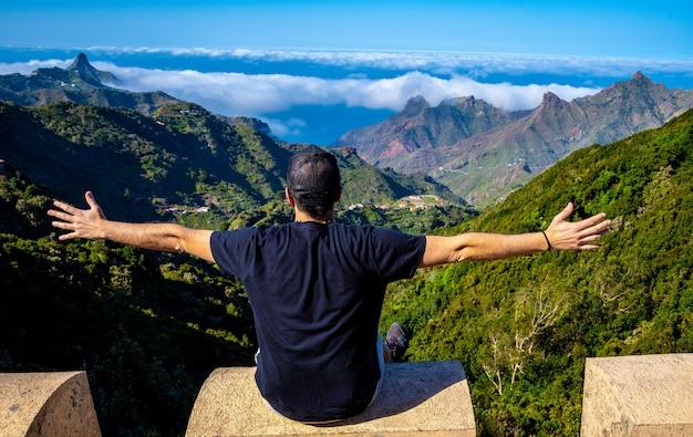 Młody mężczyzna patrząc na góry anaga na północy teneryfy w hiszpanii