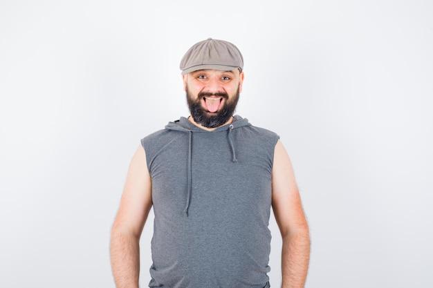Młody mężczyzna patrząc na kamery w bluzie z kapturem bez rękawów, czapce i patrząc radosny. przedni widok.