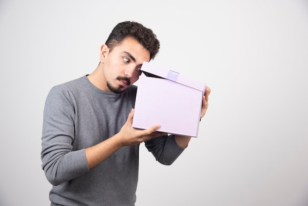 Młody mężczyzna patrząc na otwarte fioletowe pudełko na białej ścianie.