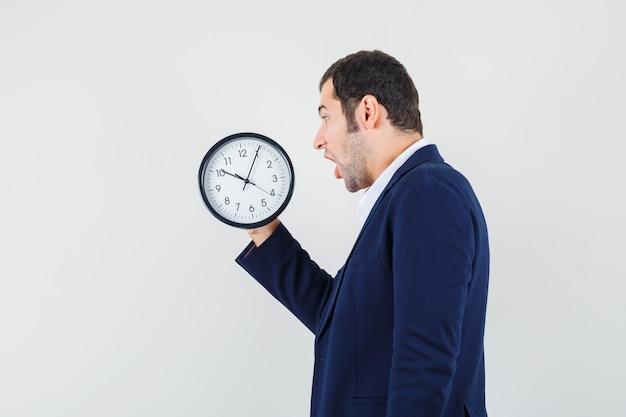 Młody mężczyzna patrząc na zegar ścienny w koszuli i kurtce i wyglądający na zdumionego.