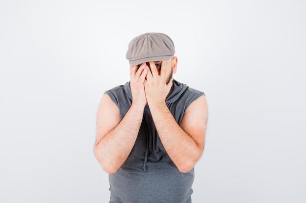 Młody mężczyzna patrząc przez palce jednym okiem w bluzie z kapturem bez rękawów, czapce i patrząc ładny, widok z przodu.