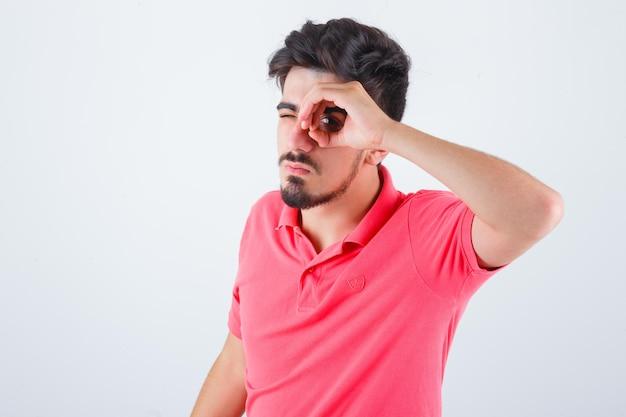 Młody mężczyzna patrząc przez palce w koszulce i patrząc śmieszny, widok z przodu.