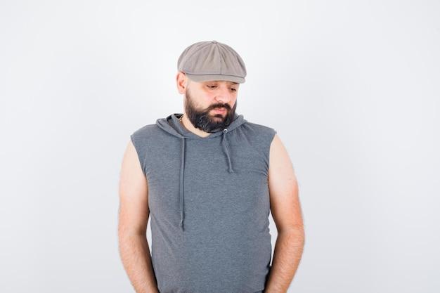 Młody mężczyzna patrząc w dół w bluzie z kapturem bez rękawów, czapce i patrząc zamyślony, widok z przodu.