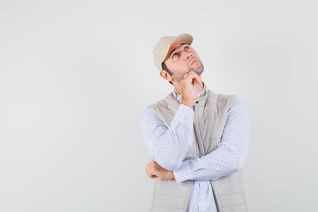 Młody mężczyzna patrząc w górę, opierając rękę w koszuli, kurtce bez rękawów, czapce i patrząc zamyślony. przedni widok. miejsce na tekst