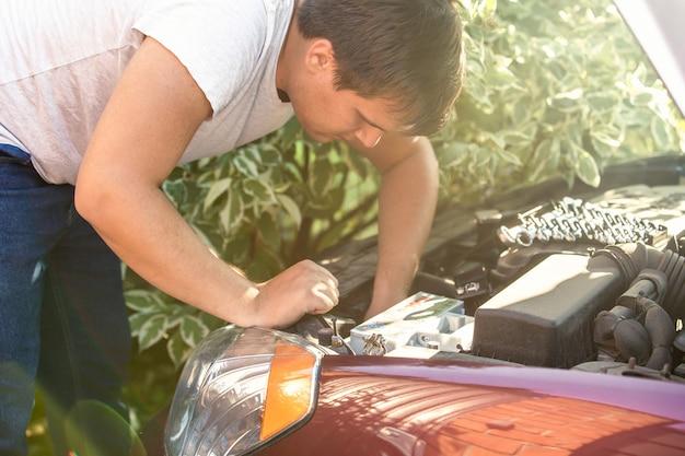 Młody mężczyzna patrzący na otwartą maskę samochodu i naprawiający silnik