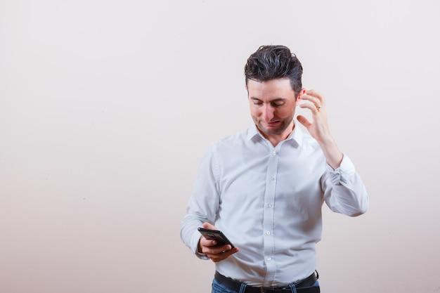 Młody mężczyzna patrzący na telefon komórkowy, myśląc w koszuli, dżinsach i wyglądając na zirytowanego