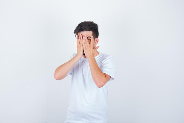 Młody mężczyzna patrzący przez palce w białej koszulce i wyglądający na przestraszonego