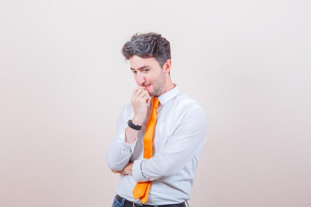 Młody mężczyzna patrzący w dół, obgryzający paznokcie w koszuli, dżinsach i patrzący zamyślony