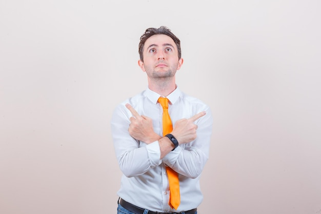 Młody mężczyzna patrzący w górę, wskazujący w białej koszuli, krawacie, dżinsach i patrzący z nadzieją