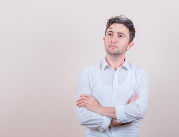 Młody mężczyzna patrzący w górę ze skrzyżowanymi rękami w białej koszuli i wyglądający na zamyślonego