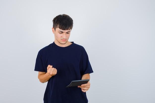 Młody mężczyzna patrzy na kalkulator, w czarnej koszulce trzyma zaciśniętą pięść i wygląda poważnie. przedni widok.