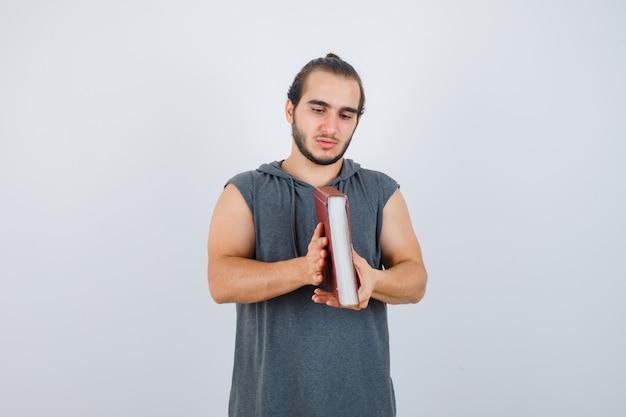 Młody mężczyzna patrzy na książkę w bluzie bez rękawów i wygląda zamyślony. przedni widok.