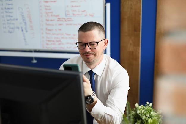 Młody mężczyzna patrzy na monitor smartfona i komputera w miejscu pracy