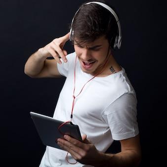 Młody mężczyzna piękne słuchanie muzyki. pojedynczo na czarno.