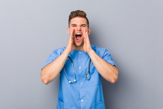 Młody mężczyzna pielęgniarka krzyczy podekscytowany do przodu.