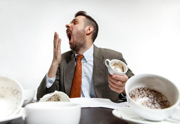 Młody mężczyzna pije dużo kawy, ale i tak nie może się obudzić i pracować. śpij dalej w biurze. pojęcie kłopotów, biznesu, problemów i stresu pracownika biurowego.