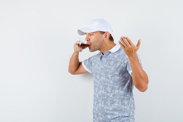 Młody mężczyzna pije herbatę w koszulce i czapce i wygląda na zachwyconego