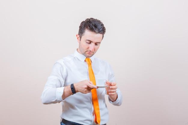 Młody mężczyzna pije po turecku kawę w białej koszuli, krawacie i wygląda ostrożnie