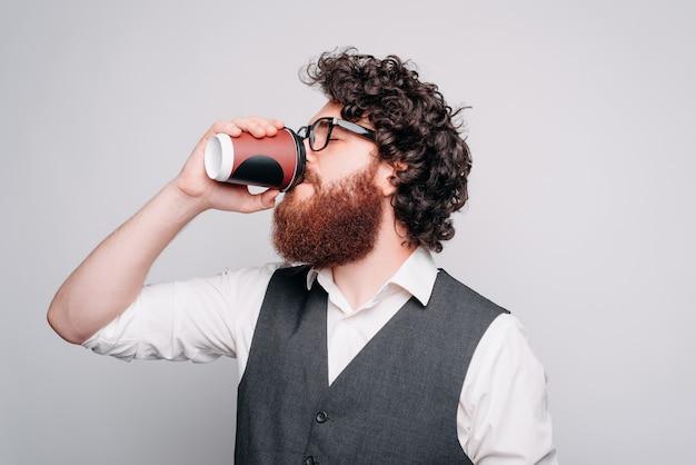 Młody mężczyzna pije z papierowego kubka w pobliżu szarej ściany