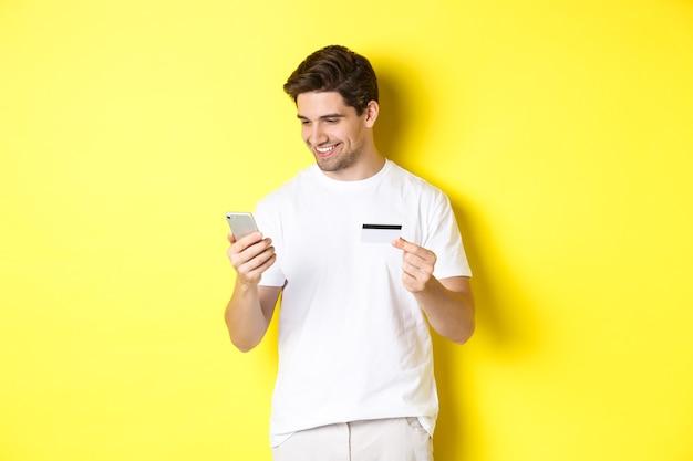 Młody mężczyzna płaci online, wstawia numer karty kredytowej na telefonie komórkowym, robi zakupy w internecie, stoi nad żółtym tłem