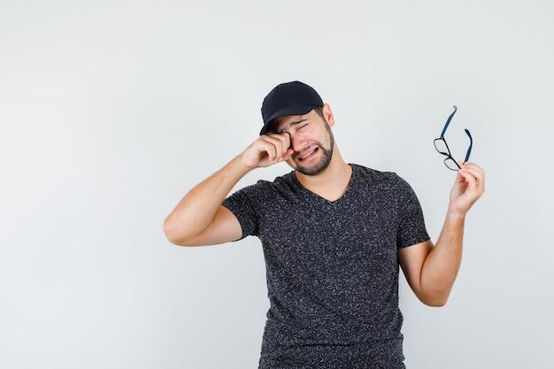 Młody mężczyzna płacze trzymając okulary w t-shirt i czapkę