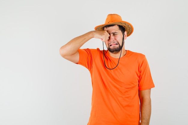 Młody mężczyzna pociera oko płacząc jak dziecko w pomarańczowej koszulce, kapeluszu i wygląda na obrażonego, widok z przodu.