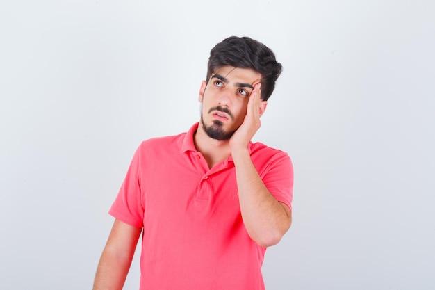 Młody mężczyzna pociera skronie w różowej koszulce i wygląda na zamyślony. przedni widok.