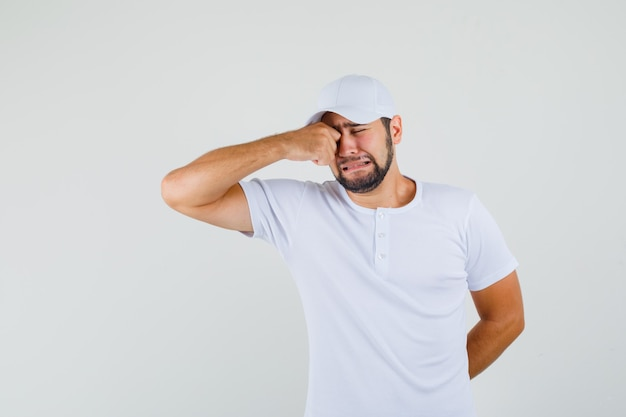 Młody mężczyzna pocierając oko płacząc w koszulce, czapce i patrząc smutno. przedni widok.