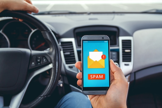 Młody mężczyzna podczas prowadzenia samochodu z telefonem w ręku.